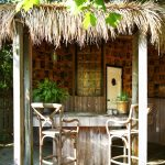 Ethnic Outdoor Wet Bar With Wooden Table And Stools And Walls With Pictures