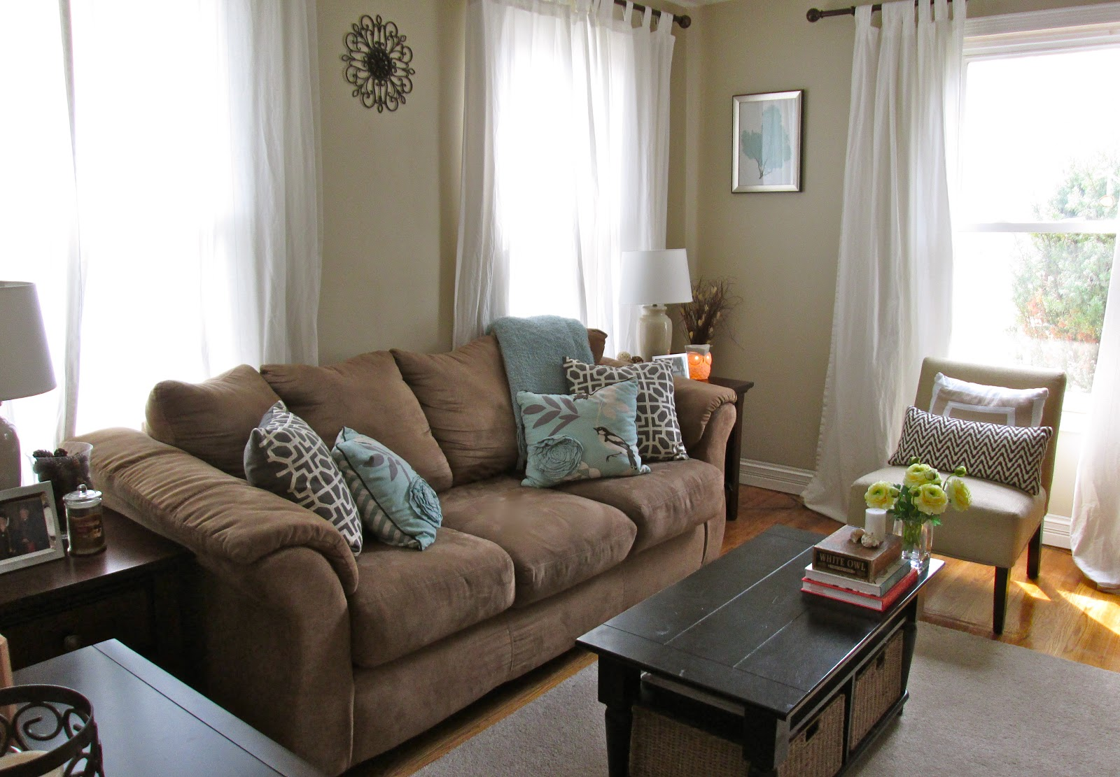 comfortable dark grey sofa decorative pillows light grey reading chair with monochromatic pillow dark wooden table with rattan basket underneath