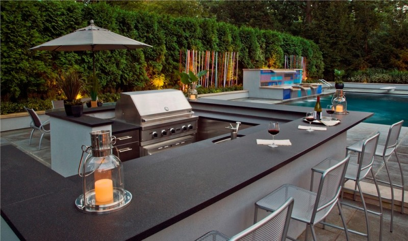 contemporary modern black outdoor wet bar with barbeque tools beside a pool
