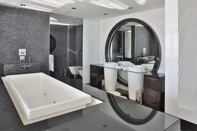 elegant spacious bathroom rectangular modern bathtub circular mirror marble patterned wall two long standing futuristic washbasins