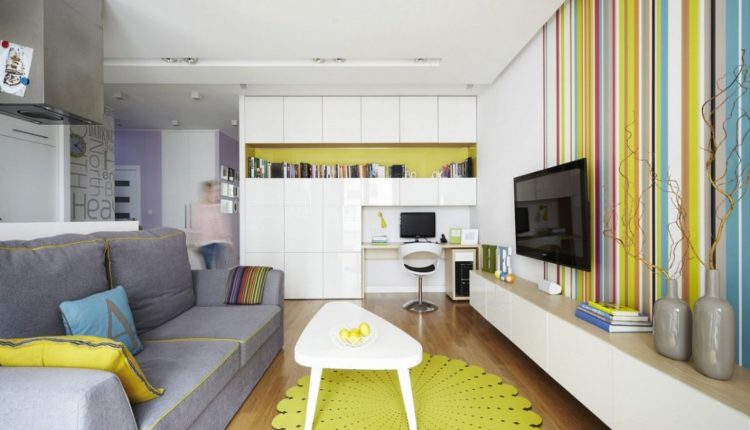 grey sofa with armrest decorative pillows unique white coffee table unique yellow carpet wall mounted TV floating white TV console colorful strips wallpaper