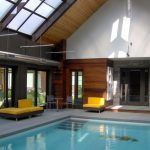 Indoor Pool With Basketball Ring Wooden Walls Glass Door Modern Poolside Chairs Table Brown And Yellow Sofa