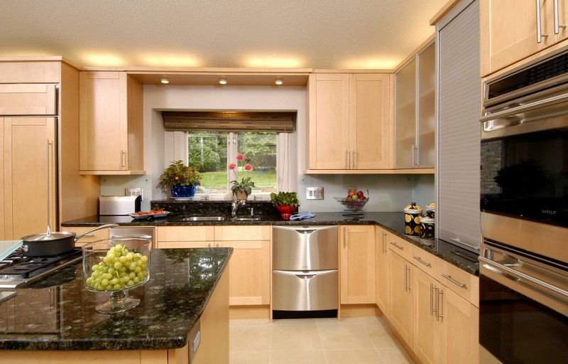 large kitchen with light brown wooden cabinet adn lamp above