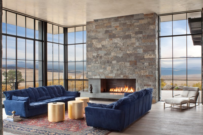 modern house interior blue sofas wooden floor glass windows carpet books gold colored tables fireplace