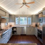 Modern White And Spacious Kitchen With Fan In The Ceiling And LED Lighting Above The Cabinet