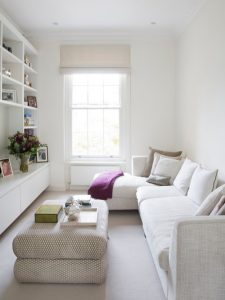 purely white sofa white ornamental pillows unique table huge vertical book shelves in white