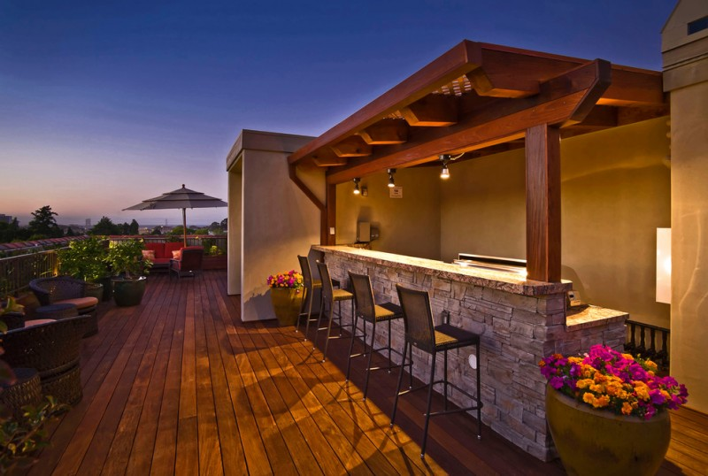 romantic wooden terrace with couples of rattan comfort chair and sofas under big umbrella and marmer wet bar and high bamboo stool