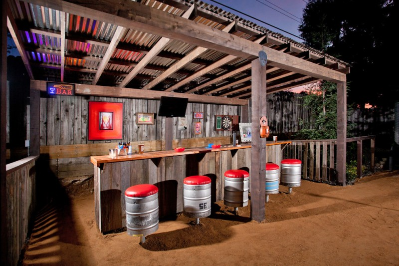 rustic wooden outdoor wet bar with stools made of silver barrel with red pillows and red painting and TV