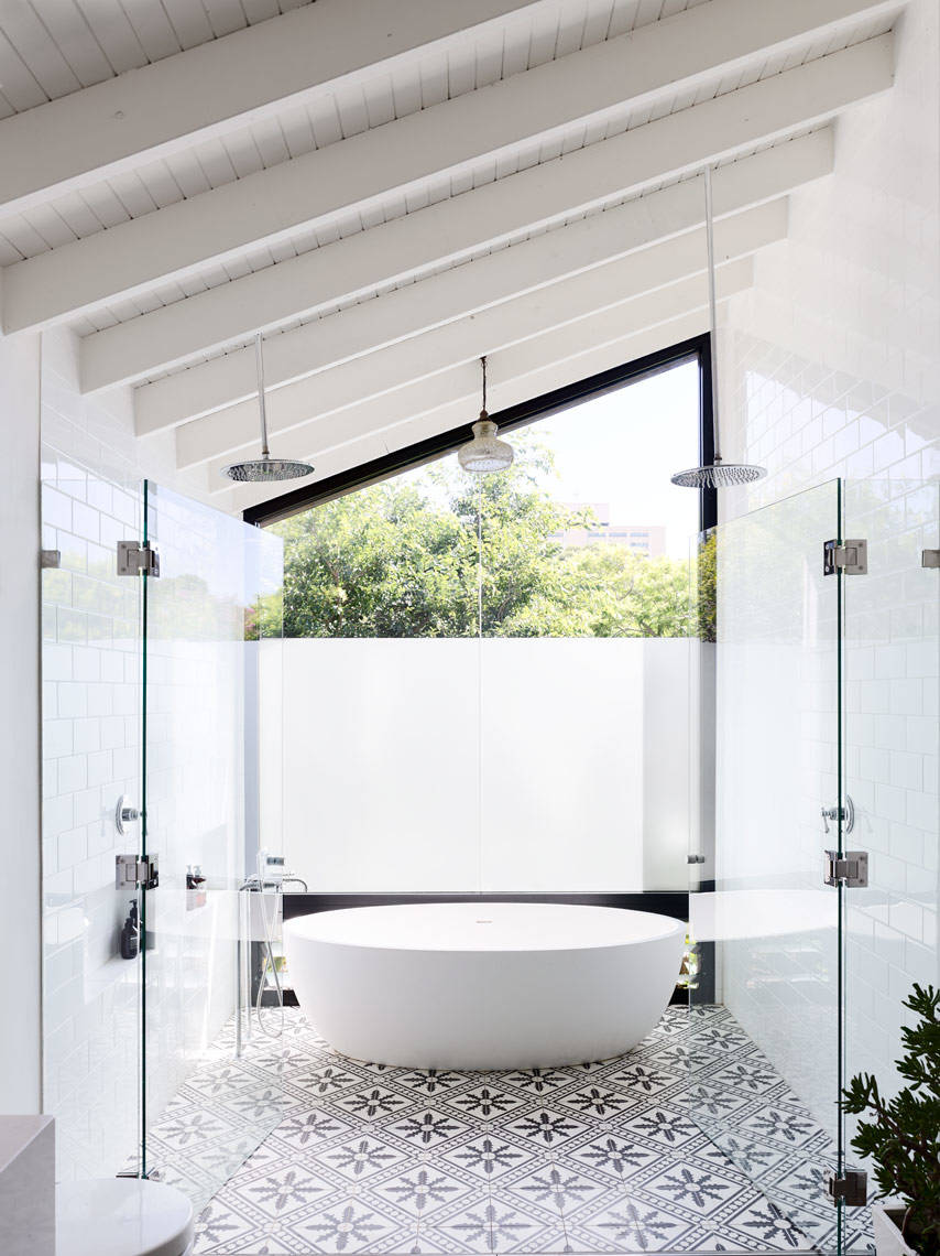 slanted white roof patterned floor tiles glass door free standing oval bathtub double ceiling shower