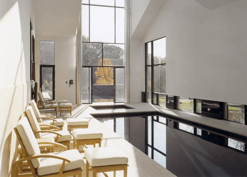 small indoor pool poolside chairs soaring glass window glass door white walls white ceiling landscape
