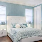 Teal Bedding With Rose Pilow And Two Standard Pillows And Tufted Leather Bed