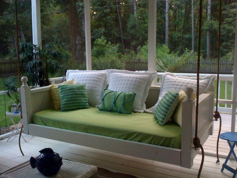 white wooden bed swing with fresh green cushion and green white pillows