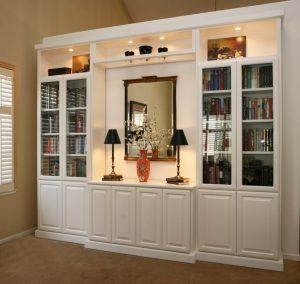 white wooden built in niches with shelves and cabinet in the middle