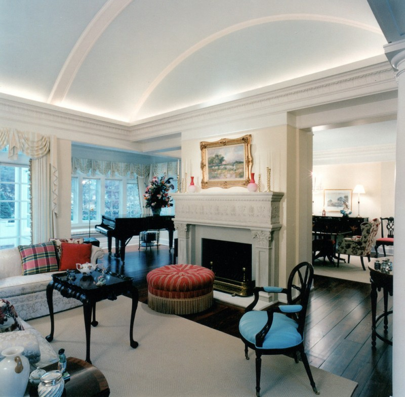 Barrel vaulted living room with white ceiling and wall, dark wood flooring, white fire place, blue chair, red ottoman