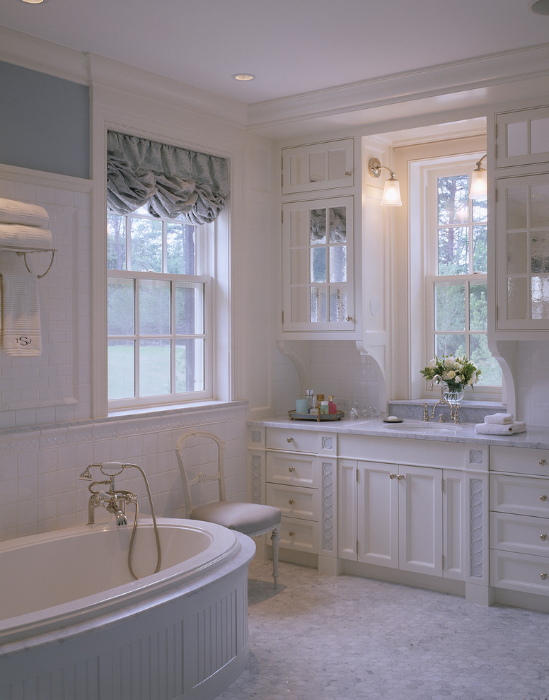 Roman sytle bathroom design with white bathtub white countertop and white cabinets upper cabinetry with glass door white marble floors grey half window curtain with decorative base