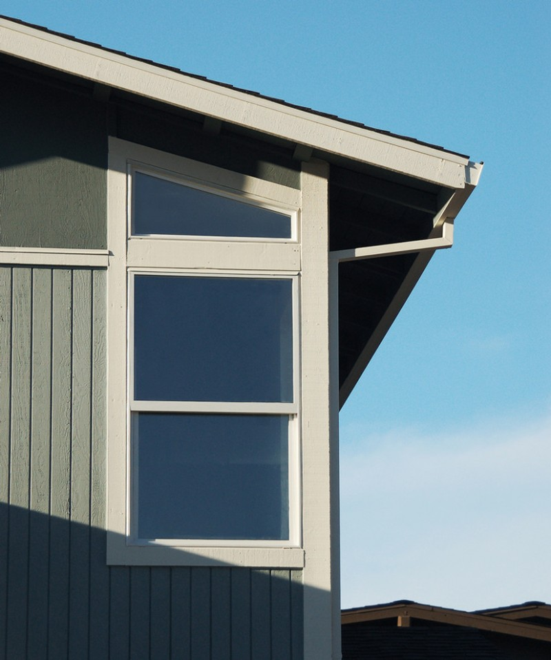 angled exterior window idea with white window frames and fascia trims