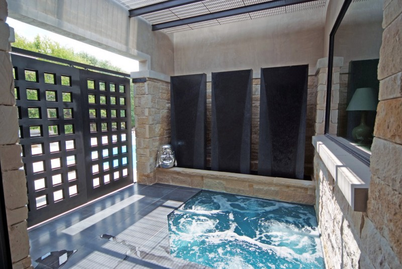 asian built in ground hot tub with black metal fence