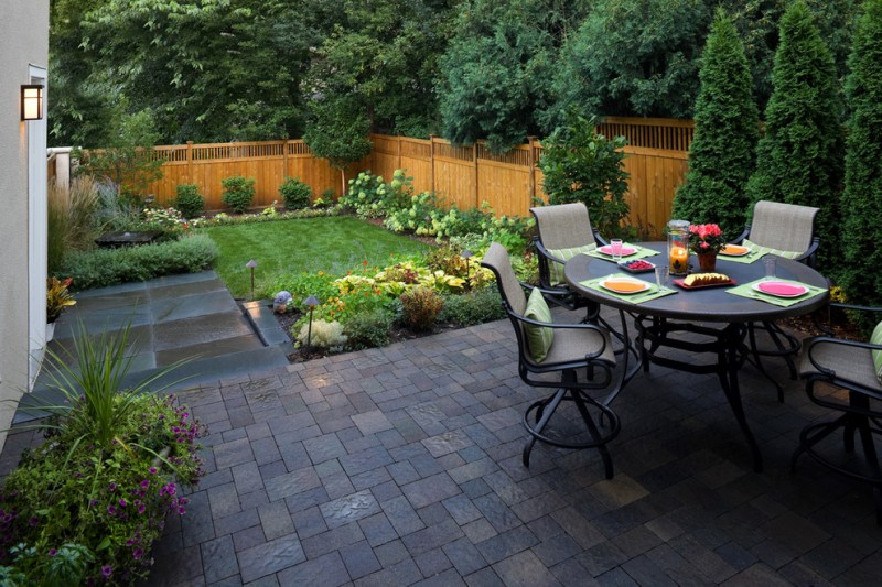 backyard with bluestone floor dining area, flowers and trees, brown and blue gray pave stone, wooden rails