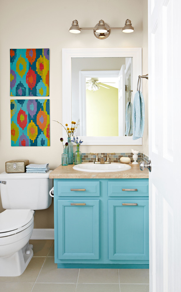 bahtroom with brown tile floorin, white wall, white toilet, turquoise cabinet with brown top and white sink, silver sconces on top of the mirror
