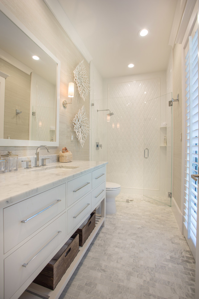 bathroom vanity with marble top undermount sink white framed mirror white washed tiles floors white toilet white diamond shape walls
