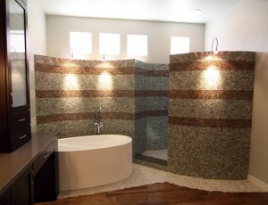 bathroom with walk in showers without door built from mosaic tiles in brown and grey up to the exterior wall and bathtub area