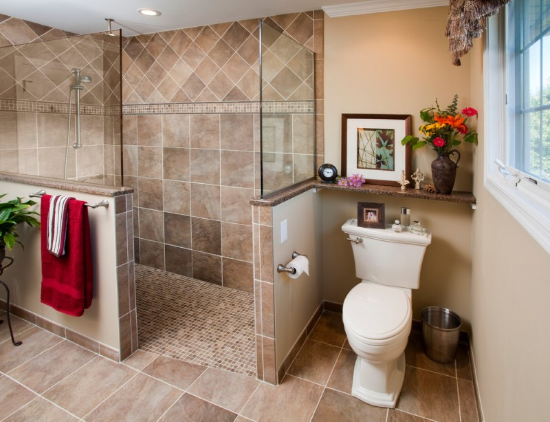 bathroom with walk in showers without door with brown tiles wall up to ceiling, half way wall with brown tiles in the bottom and glass partition in the bottom