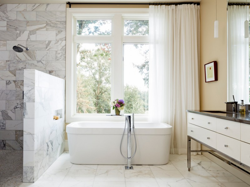bathroom with walk in showers without door with white tile up to ceiling in and white tile half wall partition