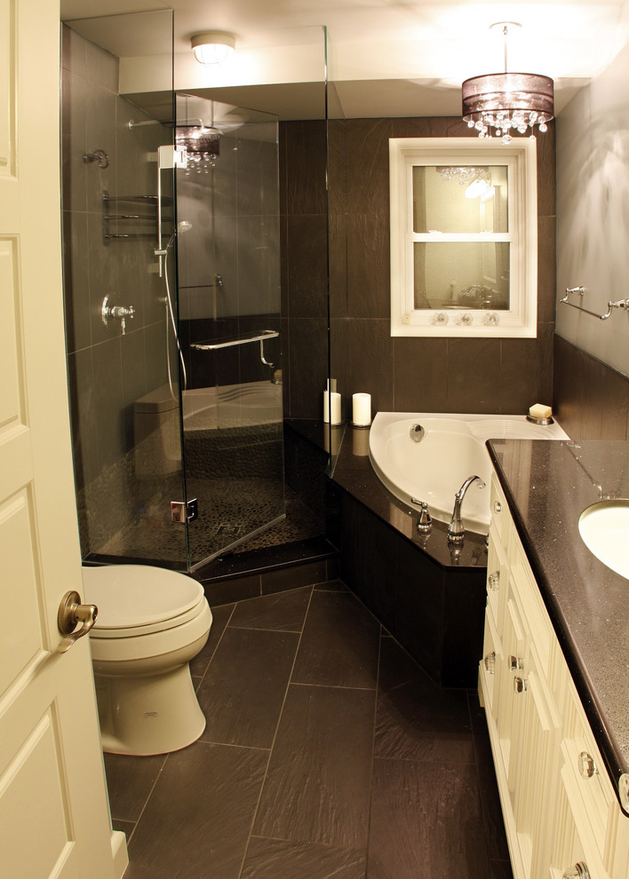 bathroom with white toilet, black tiles flooring, black marble with white tub, shower area with glass door, white cabinet under the sink, and top of the tub