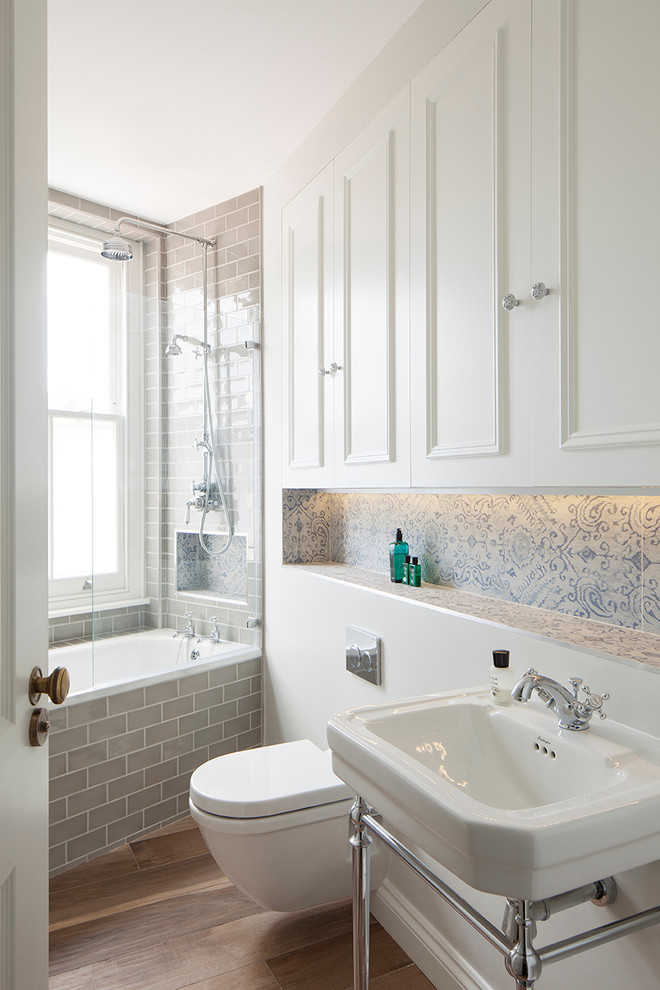 bathroom with white toilet, white cabinet on top of it, white sink, grey tiles tub area