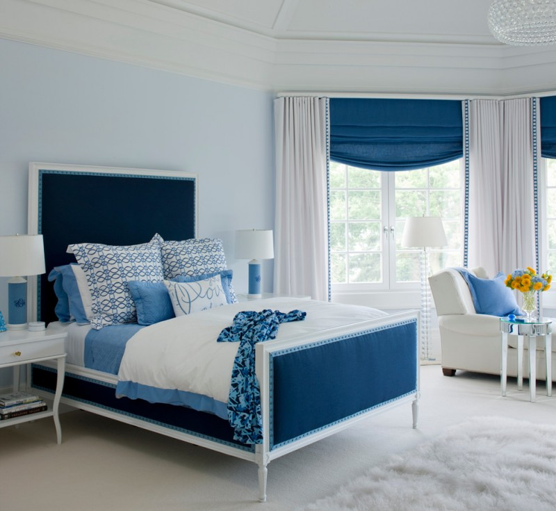 bed set with higher blue headboard accented with white frames blue white bed sheet white blanket with blue base white bedside tables with blue base white floors white flufy rug light blue walls