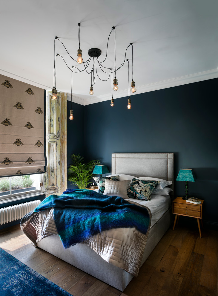 bedroom with denim blue wall, beige curtani with fly prints, wooden flooring, blue rug, azure blue cover bed, white bedding, pendant lamps aesthetically arranged