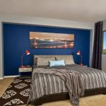 Bedroom With Grey Walls, One Side Wall In Blue, Brown Rug In The Entire Flooring, Dark Brown Rug On Top Of It, Dark Brown Bedding, Brown Grey Bed Cover, Orange Table Lamp, Navy Blue Curtain