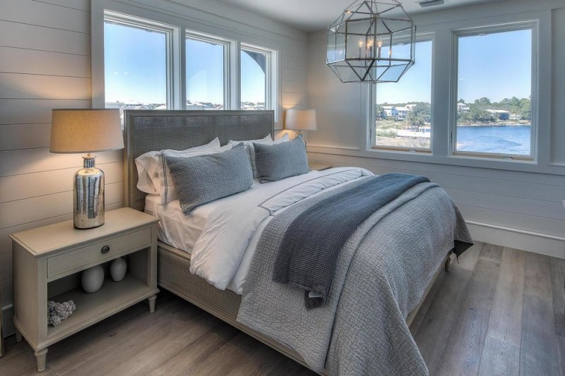 bedroom with soft blue grey wall, grey bedding, wood flooring, cream side cabinet, table lamp, pendant lamp