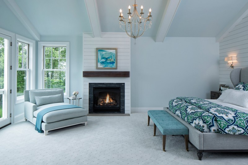 bedroom with soft blue painted wall, white horizontal wood paneled wall, blue ceiling with white wood beams, blue rug, blue lounge chair, blue bench, white bedding, blue cover, fireplace