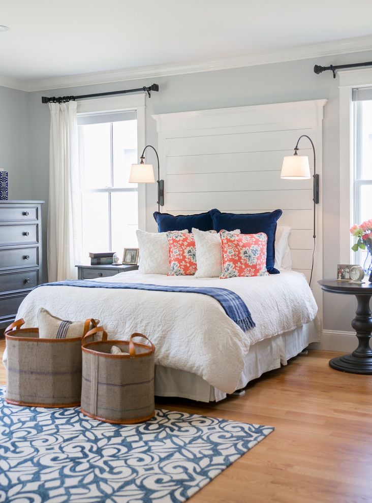 bedroom with white painted wall, white bedding, white floor lamp, wooden flooring, blue and white rug, blue cabinetry, dark wooden side table, brown laundry bag