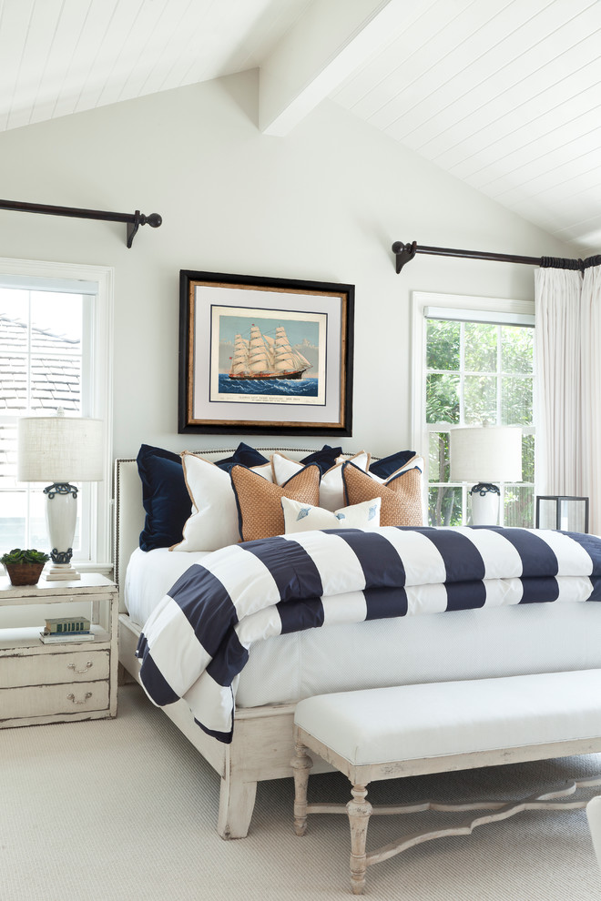 bedroom with white wall and ceiling, white bedding, white linen, white navy cover, white bench with cushion, white side cabinet, white curtains