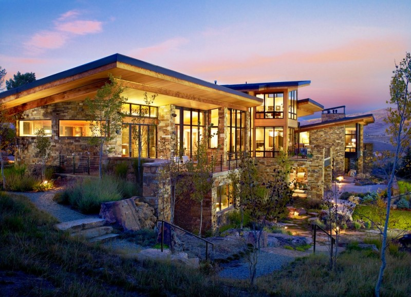 big modern mountain house with sotne exterior walls, big windows, modern and fashionable interior