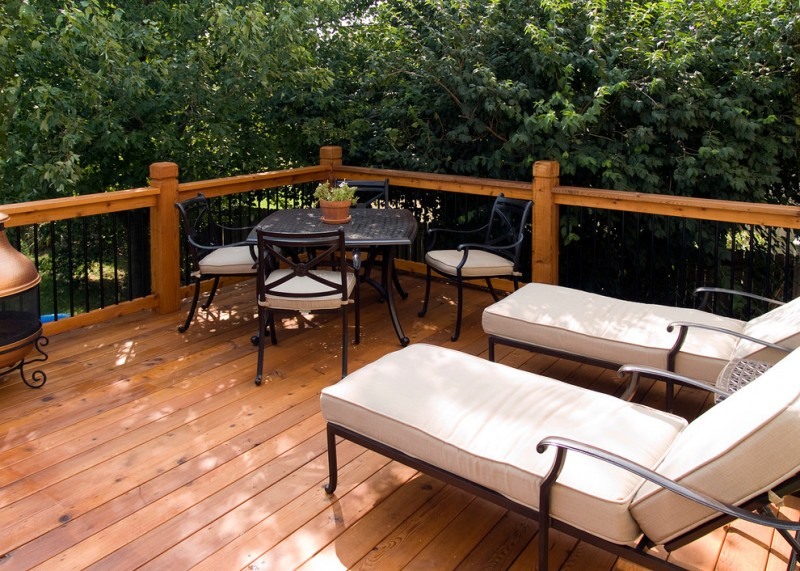 black railing system with wooden posts and stands a set of exterior furniture with black wrought iron material two exterior reclining chairs