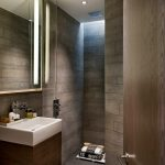 Brown Small Bahtroom With Brown Tiles Flooring And Wall, White Sink With Brown Wooden Support, Small Portion Of Glass Panel, Big Mirror