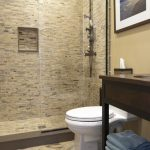 Brown Small Bathroom With Brown Tiels All Over The Shower, Brown Big Tiles In Toilet Sink Area, Glass Panel, White Toilet, Brown Wooden Sink Vanities