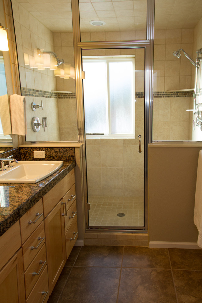 brown small master bathroom with brown cabinet, white sink and shower area separated without toilet