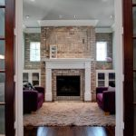 Cedar Mantle Brick Fireplace Carpet Sofa Pillows Door Glass Ceiling Lamp Wood Floor Flowers Windows