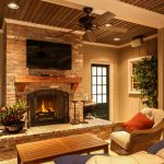 cedar mantle brick fireplace chair pillows door ceiling fan table lamp glass wall tv plant interior design