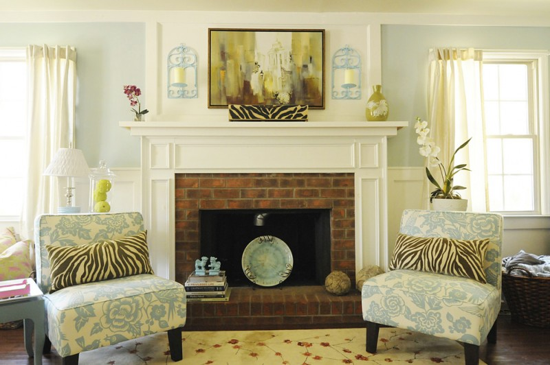 cedar mantle brick fireplace chairs pot flowers painting curtain window exposed brick light blue books basket