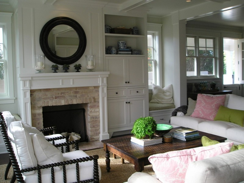 cedar mantle brick fireplace pillows sofas table windows mirror white ceiling lamp books plant glass