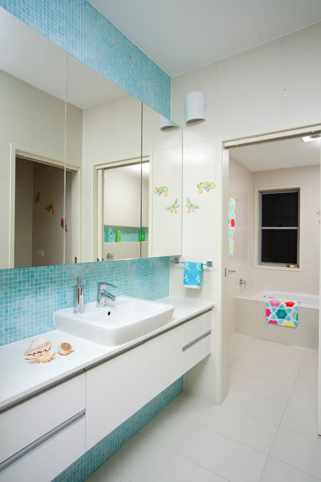 chic and modern bathroom idea with white ceramic tiles floors blue tiles walls & backsplash modern white vanity and planted sinks frameless mirror white bathtub