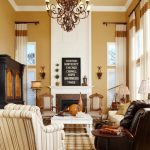 Classic & Formal Living Room With Yellow Walls Glass Windows With Half White Shutters And Half Window Curtains A Fireplace Classic Pendant Lamps Some Arm Chairs Linen Rug With Square Motifs