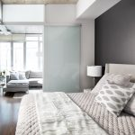 Condo With Wood Flooring With Bedroom With White Bed, Grey Wall, White Table Lamp, White Blurred Glass Sliding Door, Open To Living Room With Grey Sofa