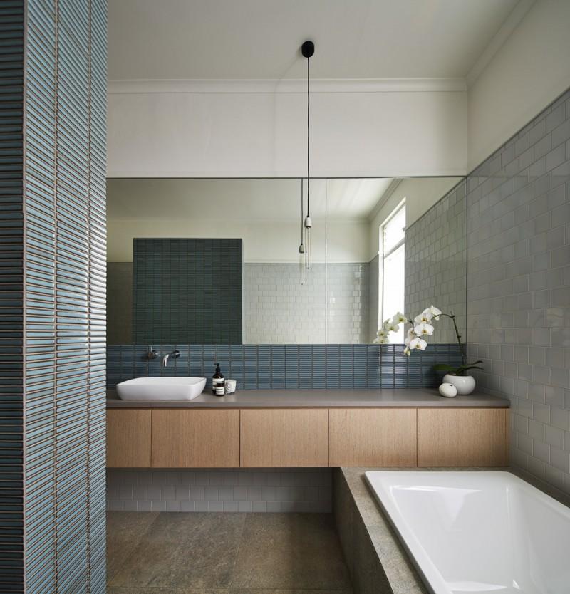 contemporary bathroom with minimalist cabinets frameless mirror white modern bathtub light blue tiles walls skiny blue backsplash natural stone tiles flooring system