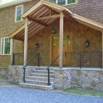 Contemporary Black Railings Idea Stone Pavings On Porch's Base Wall Wooden Siding And Wooden Front Door
